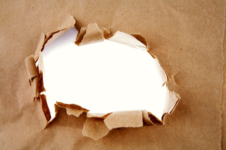 Hole ripped in brown paper photo