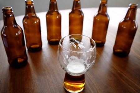 intoxicant: Bicchiere di birra e bottiglie sul tavolo