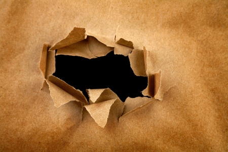 teared paper: Hole ripped in brown paper