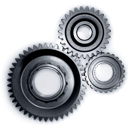 Three gears meshing together on plain background photo