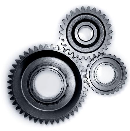cogwheel: Three gears meshing together on plain background