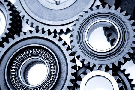 interlocked: Closeup of steel gears meshing together