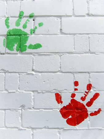 handprints: Green and red handprints on wall Stock Photo