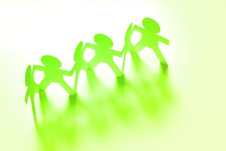 Group of paper chain people holding hands Stock Photo