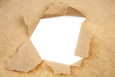 Hole ripped in brown paper on white background photo