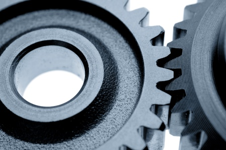 Closeup of two cogs on plain background photo