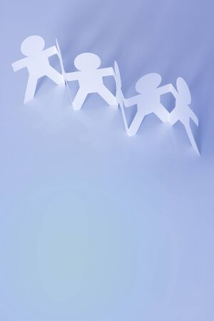 Paper doll people holding hands. Copy space photo