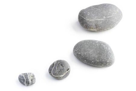 white pebble: Four assorted size rocks on plain background Stock Photo