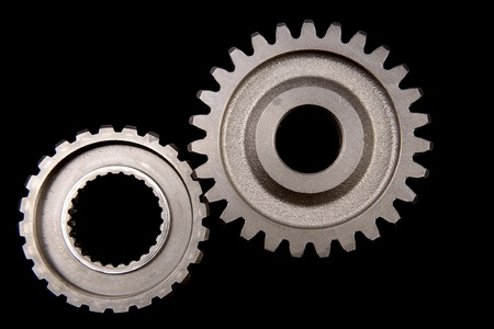 Closeup of two cogs on black photo