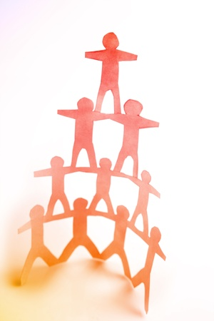 cooperative: Ten paper doll people forming a human pyramid on plain background