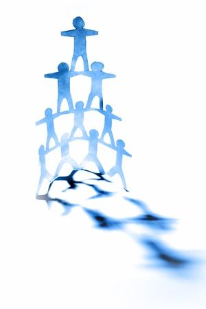 piramide humana: La gente de papel mu�ecas formando una pir�mide humana