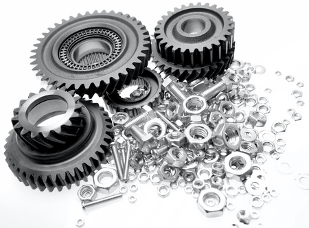 gearing: Steel gears, bolts and nuts on plain background