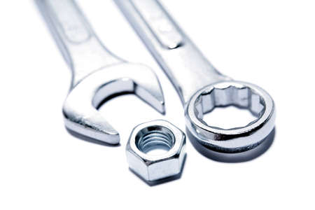 spanners: Spanners and nut on plain background Stock Photo