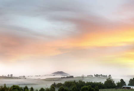 Beautiful sunrise over foggy farmland
