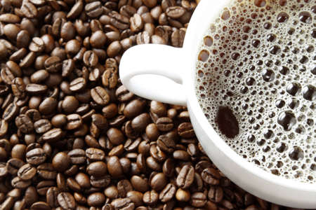 caffiene: Cup of black coffee on beans