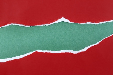 Hole ripped in red paper on green background. Copy space Stock Photo - 12876216