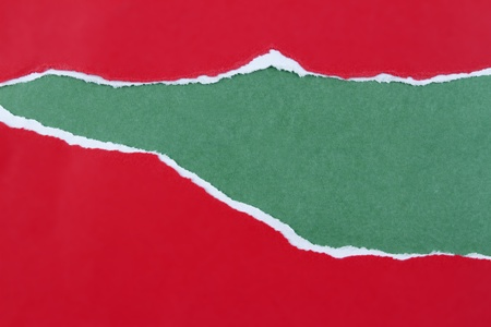 teared paper: Hole ripped in red paper on green background. Copy space