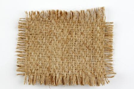 hessian: Piece of frayed burlap on plain background Stock Photo