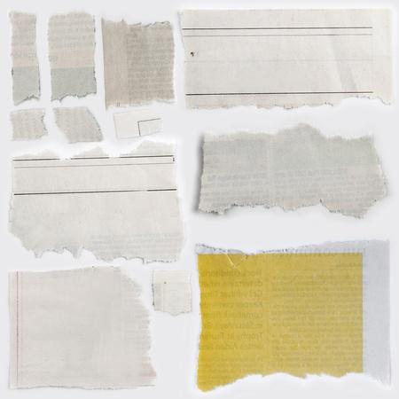 newsprint: Pieces of torn newspaper on plain background