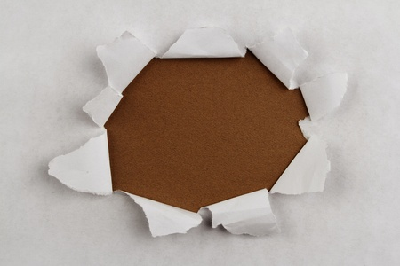 Hole ripped in paper on brown background photo