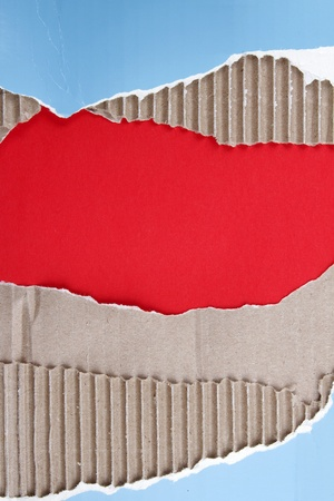 Hole ripped in corrugated cardboard on red background. Copy space photo