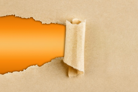 Hole ripped in brown paper on orange background  Copy space Stock Photo - 13034909