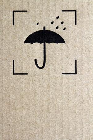 Umbrella and rain symbol on cardboard photo