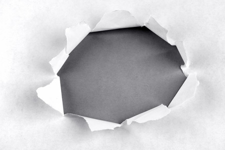 Hole ripped in paper on grey background Stock Photo - 13320120