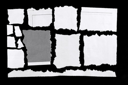 Torn pieces of paper on black background photo