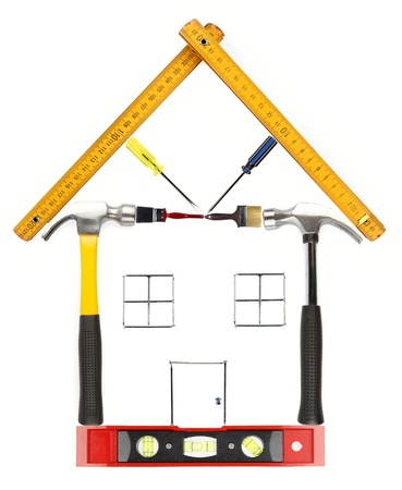 construction nails: House constructed from work tools on plain background