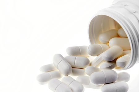 aspirin: Pills spilling from container on plain background Stock Photo