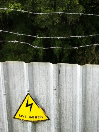 Sign on barbed wire security fence                    photo