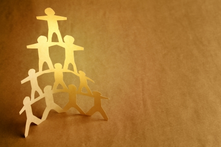 strength in unity: Human team pyramid on brown background Stock Photo