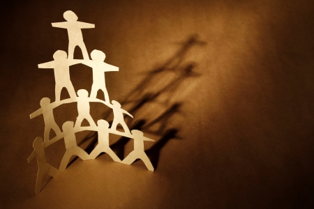 strong partnership: Human team pyramid on brown background Stock Photo