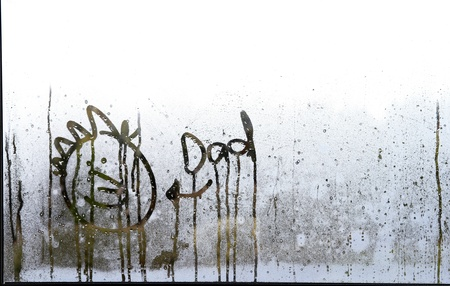 Face and word drawn in condensation on window