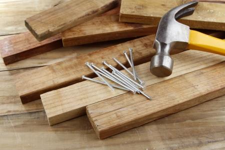the hammer: Martillo, clavos y pedazos de madera Foto de archivo