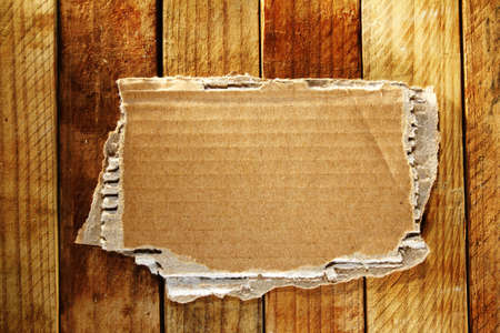 Piece of torn cardboard on boards  photo