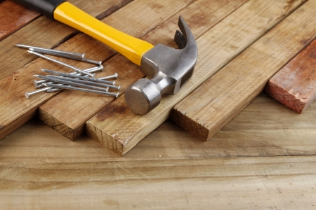 carpenter items: Hammer and nails on wood