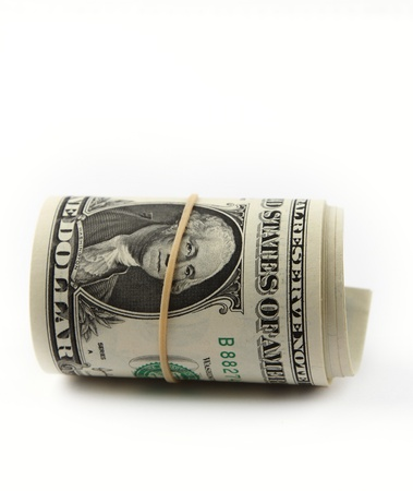 Roll of U.S. banknotes rolled up on plain background photo