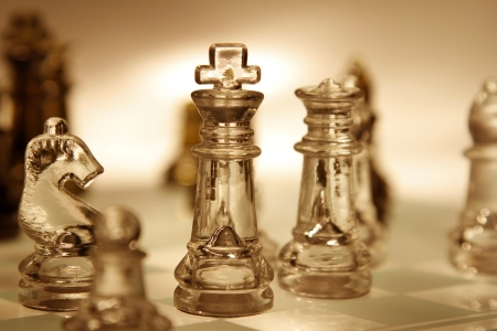 Glass chess pieces on board photo