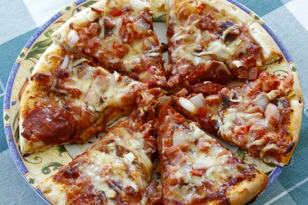 Pizza slices on plate, on tablecloth photo