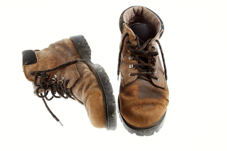 tramping: Pair of old boots on plain background