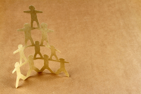 unity is strength: Human team pyramid on brown background Stock Photo
