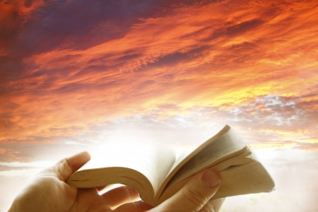 Hands holding open book on a heavenly scene photo