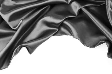 Closeup of folds in black silk fabric on white background photo