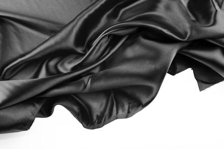 black silk: Closeup of folds in black silk fabric on white background