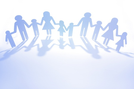 Paper doll family holding hands. Copy space Stock Photo