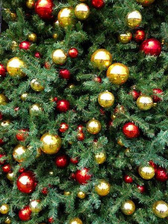 Closeup of gold and red christmas baubles on tree photo