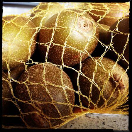 kiwifruit: Closeup of kiwifruit in net bag