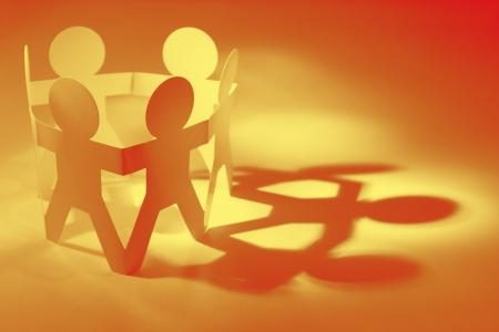 personas ayudando: Grupo de personas mu�eca de papel en un c�rculo tomados de las manos concepto trabajo en equipo